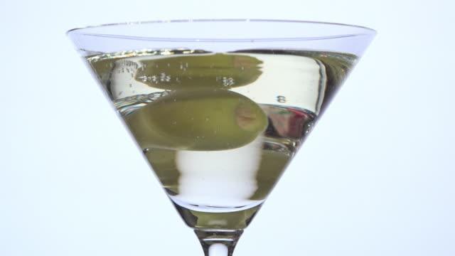 stockvideo's en b-roll-footage met gieten van droge vermout over de olijfolie - martini