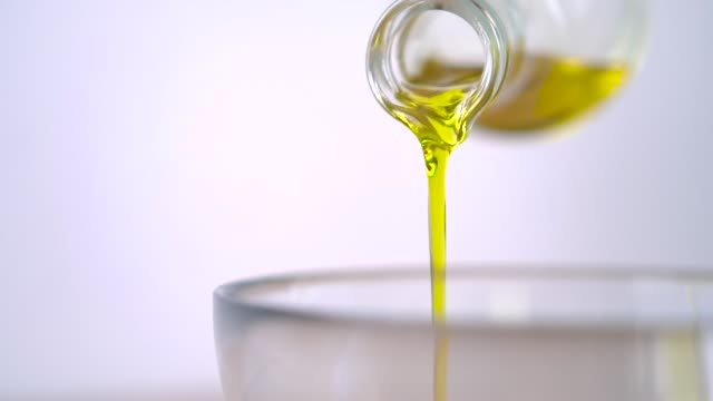 pouring virgin olive oil in glass bowl for salad in kitchen - olio d'oliva video stock e b–roll