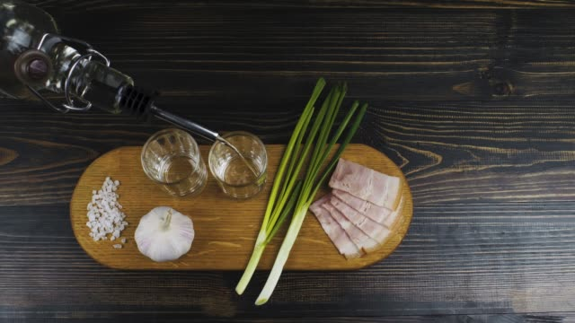 pouring vodka from a bottle into two small faceted glasses on a wooden board with green onions, garlic and bacon. view from above. russian traditions. 4k video. 59.94 fps - aglio alliacee video stock e b–roll