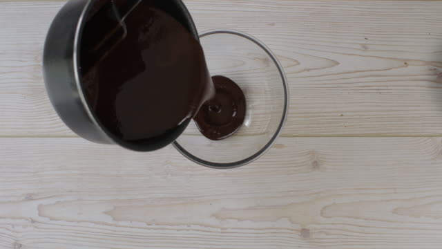 pouring warm chocolate sauce into glass bowl lock down shoot pouring warm chocolate sauce into glass bowl mixing bowl stock videos & royalty-free footage