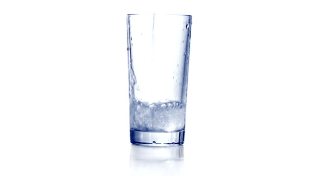 Pouring water in empty glass and adding some ice video