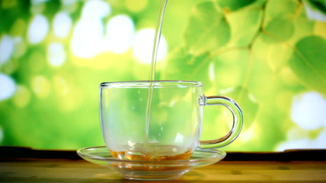 Pouring water in glass tea cup video