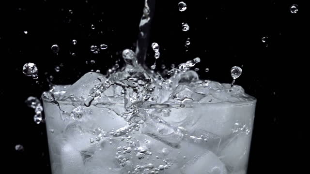 Pouring water into glass of ice with splashes at slow motion on a black background
