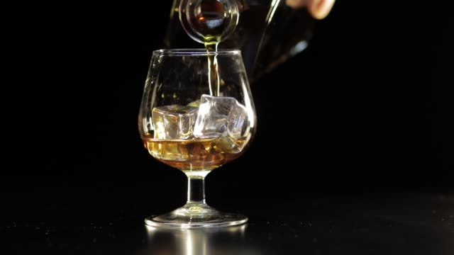pouring whiskey, cognac into glass. black background. pour of alcohol drink - brandy video stock e b–roll
