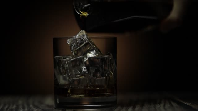 pouring whiskey, cognac into glass. dark background. pour of alcohol drink - scotch whisky video stock e b–roll