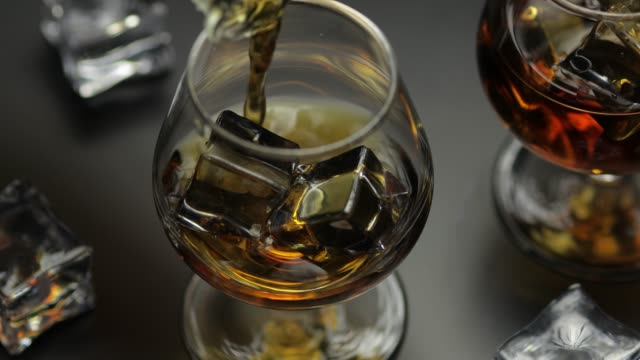 pouring whiskey, cognac into glass with ice cubes. pour of alcohol drink - scotch whisky video stock e b–roll