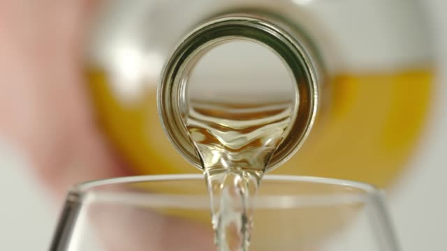 slow motion:pouring whiskey from a bottle in a glass - macro - rum superalcolico video stock e b–roll