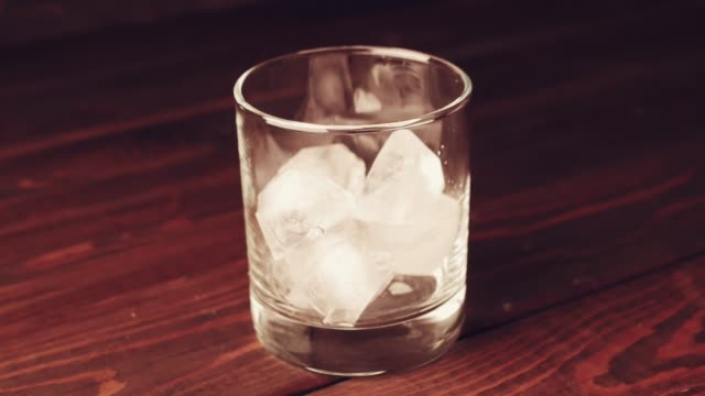 pouring whiskey in glass with cubes of ice on dark background close up - rum superalcolico video stock e b–roll