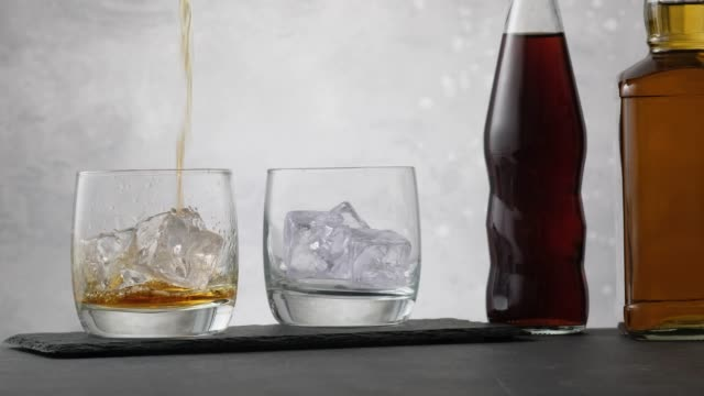 vídeos de stock e filmes b-roll de pouring whiskey in glass with ice cubes on background two bottle with cola - rum bebida branca
