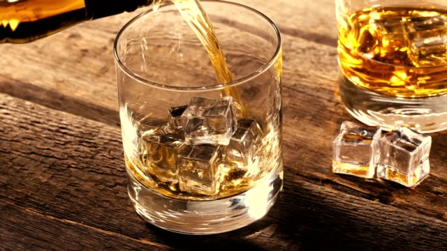 pouring whiskey into a glass with ice cubes on old wooden table