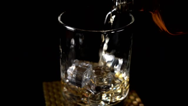 pouring whiskey into a glass with ice cubes on wooden table - brandy video stock e b–roll