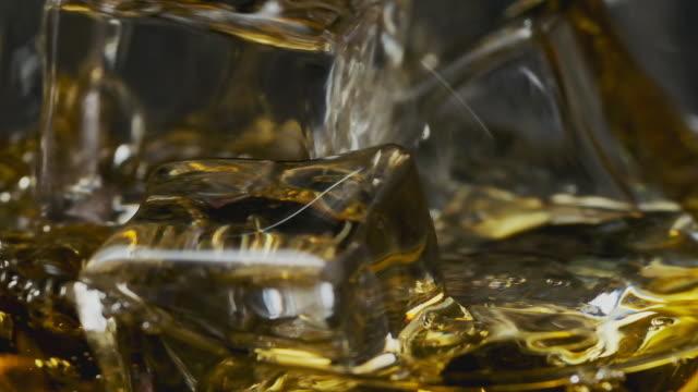 vídeos de stock e filmes b-roll de pouring whiskey or rum into glass. macro shot of scotch with ice cubes - bebida fresca