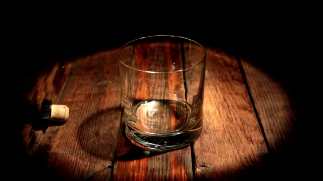 pouring whisky from the bottle on black background in the beam of light. glass of rum alcohol - scotch whisky video stock e b–roll