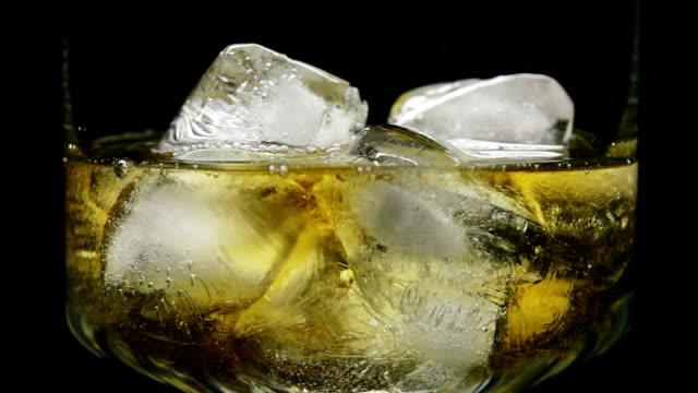 vídeos de stock e filmes b-roll de verter whisky com gelo em vidro, close-up - bebida fresca