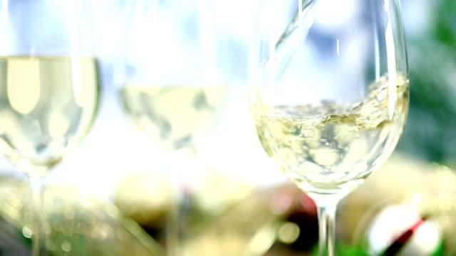 hälla vitt vin på julfest. - vitt vin glas bildbanksvideor och videomaterial från bakom kulisserna