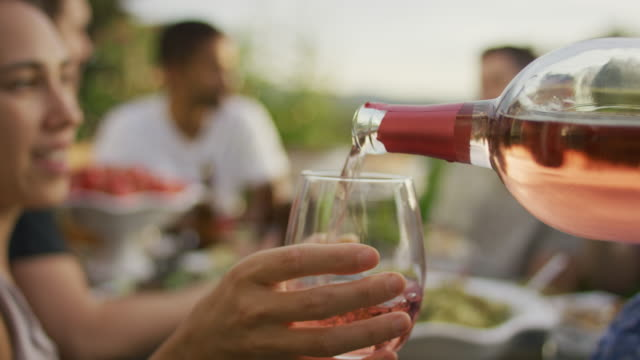 Pouring wine at an outdoor dinner party