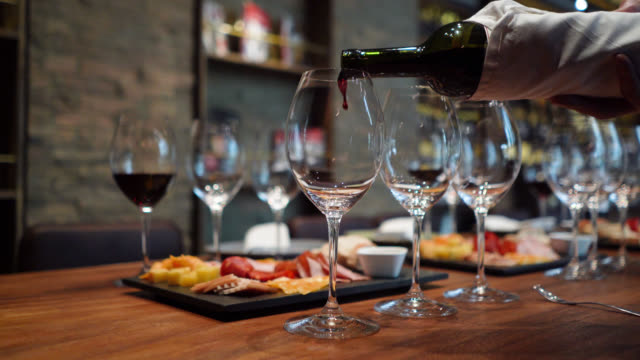 Pouring wine in glass setting a table for a wine tasting at a cellar Pouring wine in glass setting a table for a wine tasting at a cellar - Close up shot red wine stock videos & royalty-free footage