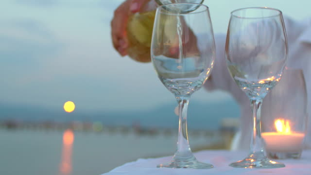 Pouring wine in glasses at seaside video
