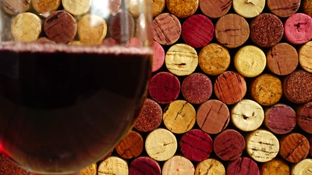 Pouring wine into a glass against the background of wine corks. Pouring wine into a glass against the background of wine corks. cork stopper stock videos & royalty-free footage