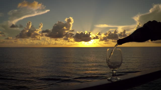 Pouring Wine on the Water Wine is poured into a glass on a ship's railing while the luxury ocean craft steams across open water. yacht stock videos & royalty-free footage