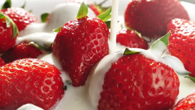 vídeos de stock e filmes b-roll de pouring yogurt onto strawberries in super slow motion - strawberry