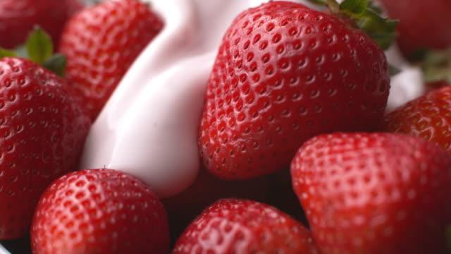 Pouring yogurt onto strawberries