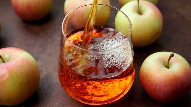 pours Apple juice into a glass Cup close up selective focus