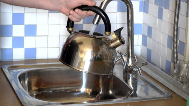 pours water into a kettle from a tap - teapot stock videos & royalty-free footage