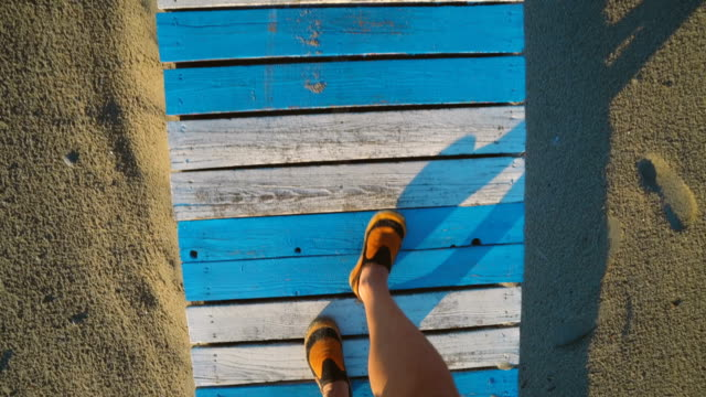 Pov looking down on pair of feet in orange sneakers walking on wooden footpath covered by sand. Summer vacation at sea beach