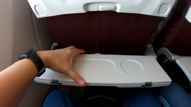 pov of hand open food tray infront of airplane seat while traveling