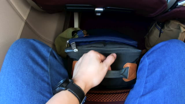 pov of hand push backpack under airplane seat before take off from ground.travel transportation - sotto video stock e b–roll