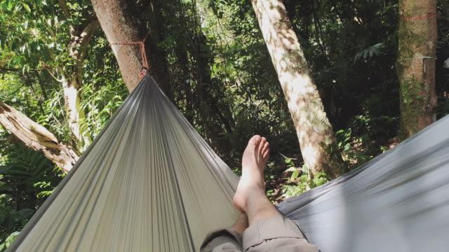 pov of people sleep on hammock in rainforest while trekking - amaca video stock e b–roll