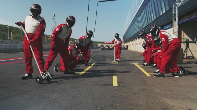 vídeos de stock e filmes b-roll de pov of racecar reaching towards technicians - dedicação