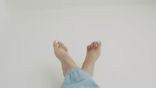 pov of woman is wiggle toes with while nail with blue pants on white background-minimal hipster of pov - dito del piede video stock e b–roll