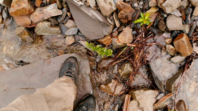 Pov view of the legs with hicking shoes of the man that walking on stones