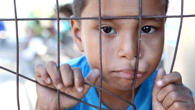 HD poverty - Asian boy behind fence video