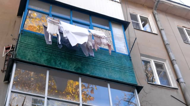 Poverty life concept. Linen is dried on the balcony on the street.