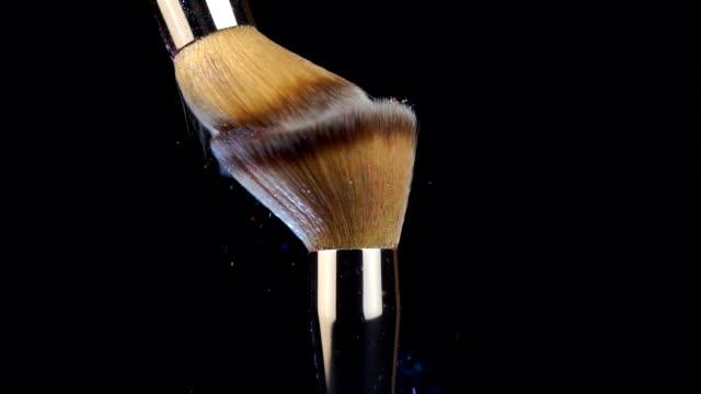 vidéos et rushes de brosse de poudre sur le fond noir avec l'éclaboussure colorée de poudre se ferment vers le haut - pinceau à maquillage