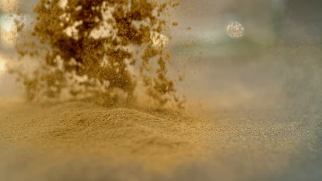SLO MO LD Powdered ginger falling onto a surface Slow motion close up locked down shot of powdered ginger falling onto a flat surface. Shot in Slovenia. ginger spice stock videos & royalty-free footage