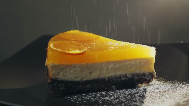 powdered sugar falls on top of a cake and a plate in slow motion - sostanza gelatinosa video stock e b–roll