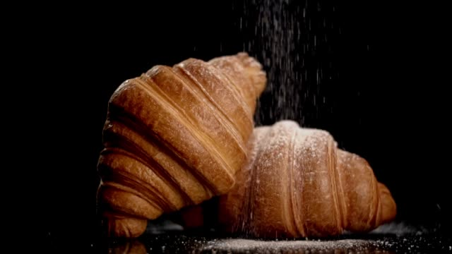 powdered sugar sprinkling onto croissant in slow motion on black background - background food video stock e b–roll