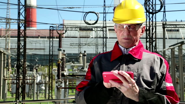 Power engineering specialist with red smartphone at electropower station video