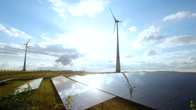 power generating wind turbines and modern solar panels in the countryside