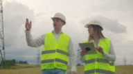 istock Power lines, a man and a woman engineers with a tablet in their hands discussing the progress of the construction project. 1166358085