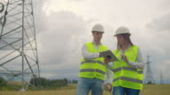 istock Power lines, a man and a woman engineers with a tablet in their hands discussing the progress of the construction project. 1166361630