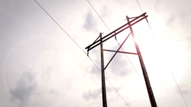 Power Lines with lens flare in cloudy sky video
