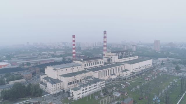 stockvideo's en b-roll-footage met elektriciteitscentrale met leidingen en de stad gehuld in rook. luchtverontreiniging en milieuproblemen. - lood