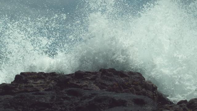 slow motion: powerful ocean swell hits the black rocky shore and splashes in air - wielki filmów i materiałów b-roll