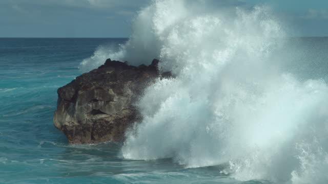 SLOW MOTION: Powerful ocean wave splashes across a big rock in the middle of sea