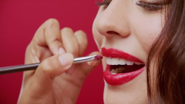 kraftfull röd för en kraftfull vitlinglyra - makeup artist bildbanksvideor och videomaterial från bakom kulisserna